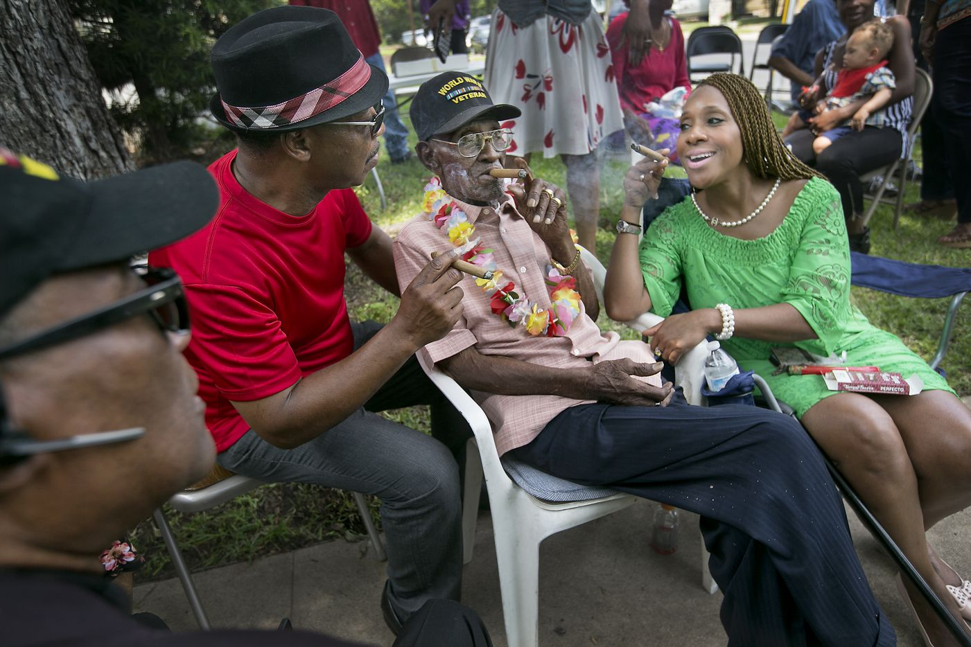 WWII veteran Richard Overton celebrates his 110th birthday in May 2016 with friends and family at his home in Austin.  He smokes a cigar with caregiver Martin Wilford (left) and good friend  Donna Shorts. Pastor Carl Jarman (far left) sits nearby.