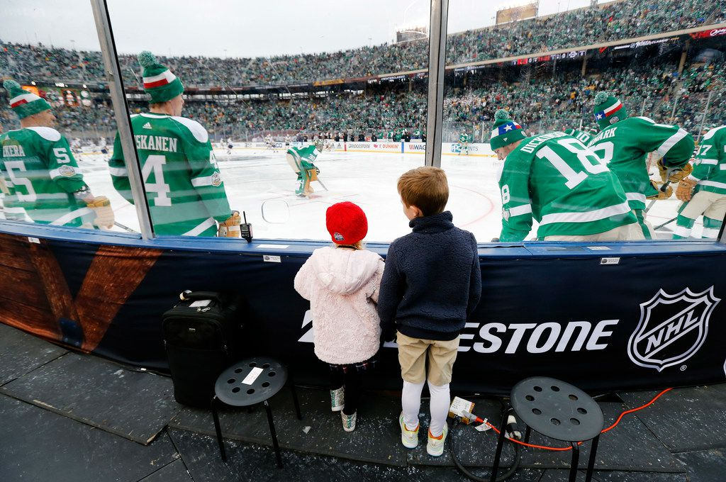 Graeme and Ryanne Egan of Dallas watch the Dallas Stars warm up on the ice before their outdoor NHL Winter Classic hockey game with the Nashville Predators at the Cotton Bowl in Dallas, Wednesday, January 1, 2019. (Tom Fox/The Dallas Morning News)