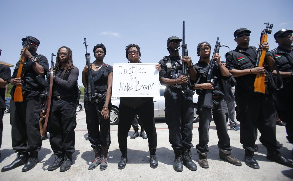Huey P. Newton Gun Club members and community activists stop for a break in the parking lot of Elaine's Kitchen during the first of its armed self defense patrols in southern Dallas, in 2014.