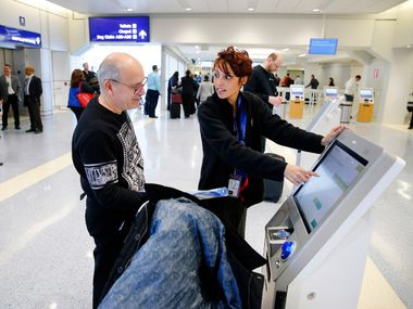 American Airlines customer care representative Season Farmer (right) assists passenger Gennadi Finkelshtain of Israel with a kiosk check-in at the newly renovated check-in area of Terminal A, Thursday, January 25, 2017. Dallas-Fort Worth International Airport officials showed off their newly completed renovations to Terminal A, the first of several terminals receiving a makeover. (Tom Fox/The Dallas Morning News)