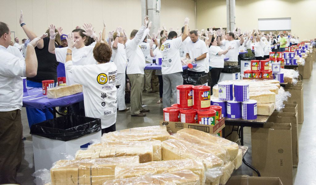 Volunteers raise their hands in the air just before the start of the Guinness World Record Spreading Party. During the party volunteers used an assembly line to make as many PB&J sandwiches as possible in one hour.