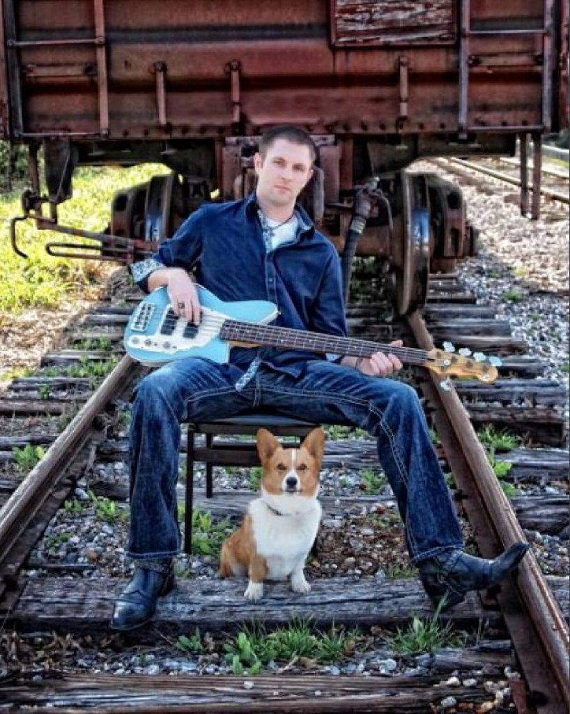 """Jonathan Crews poses with his guitar and his Corgi, Ulysses. His father, John Crews, described him as a """"Renaissance man"""" who was well-read and sought adventure."""