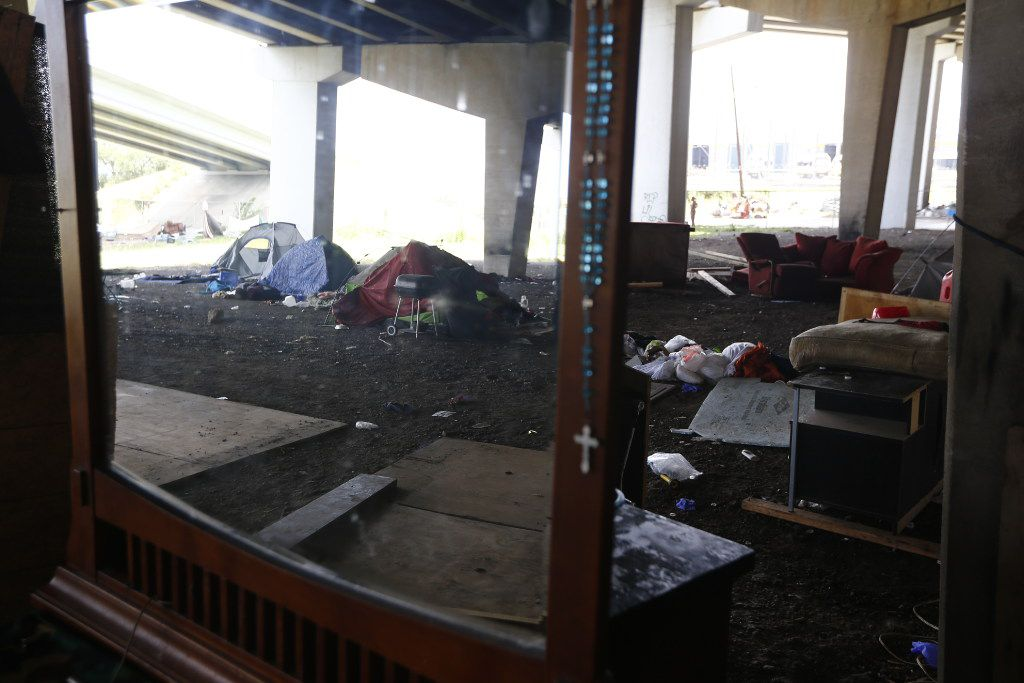 A mirrored cabinet is left to be thrown away in a large homeless encampment under that was shut down under Interstate 30 on 3rd Avenue in Dallas on July 25, 2017.