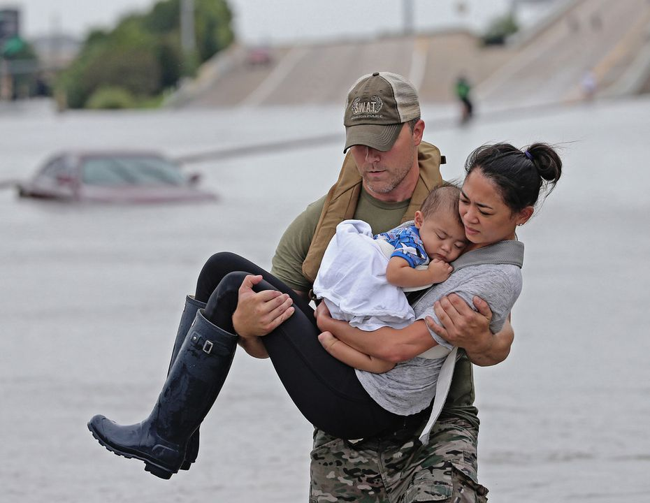 Photographer Louis DeLuca was honored for images that included this one taken in the wake of Hurricane Harvey. The image showed Houston SWAT Officer Daryl Hudeck carrying Catherine Pham and her 13-month-old son, Aidan, to safety after they were rescued by boat from flooding in Houston.