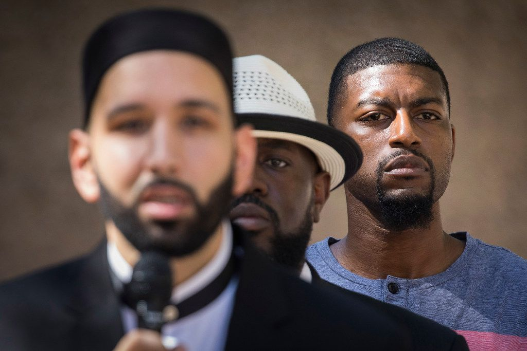 Odell Edwards, the father of Jordan Edwards, a 15-year-old who was killed by a Balch Springs police officer in April, stands behind the Rev. Michael W. Waters as they listen while Imam Omar Suleiman addresses a day of remembrance for last year's police ambush.