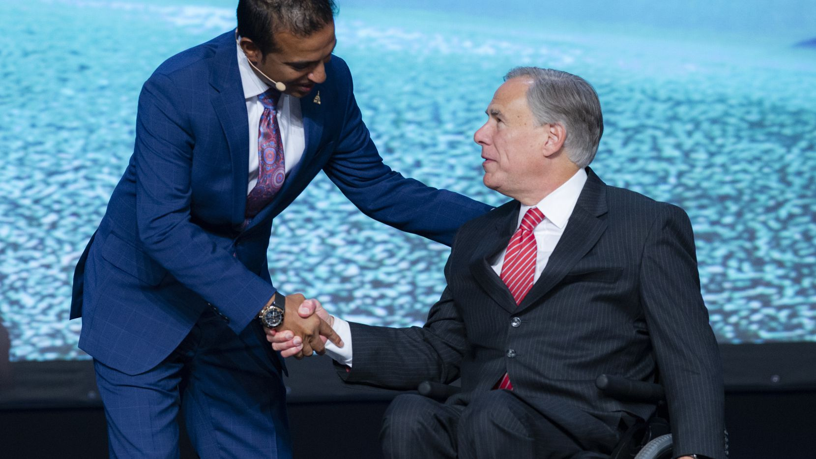 Asian American Hotel Owners Association Chairman Biran Patel, left, greets Texas Gov. Greg Abbott as the keynote speaker of the AAHOA convention in Dallas, Wednesday, August 4, 2021. (Brandon Wade/Special Contributor)