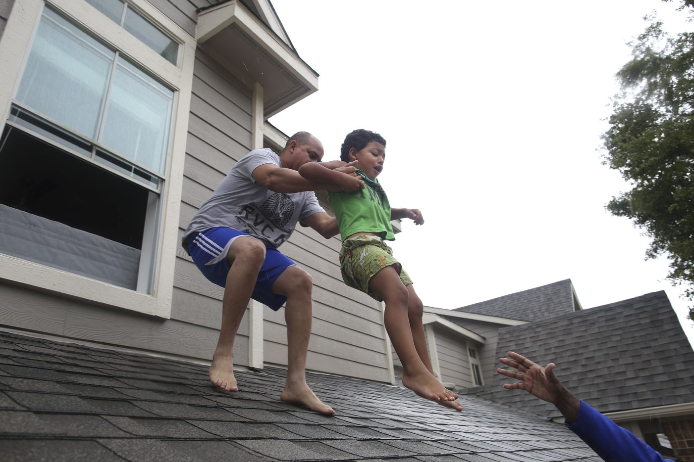 Castiel Torres, 3, is helped off of his roof by family friend Dagoberto Ordonez, left, into a waiting boat after the area flooded in Houston, Aug. 29, 2017. As one of the most destructive storms in the nation's history pummeled southeast Texas for a fourth day, forecasts on Tuesday called for still more rain, making clear that catastrophic flooding that had turned neighborhoods into lakes was just the start of a disaster that would take years to overcome.