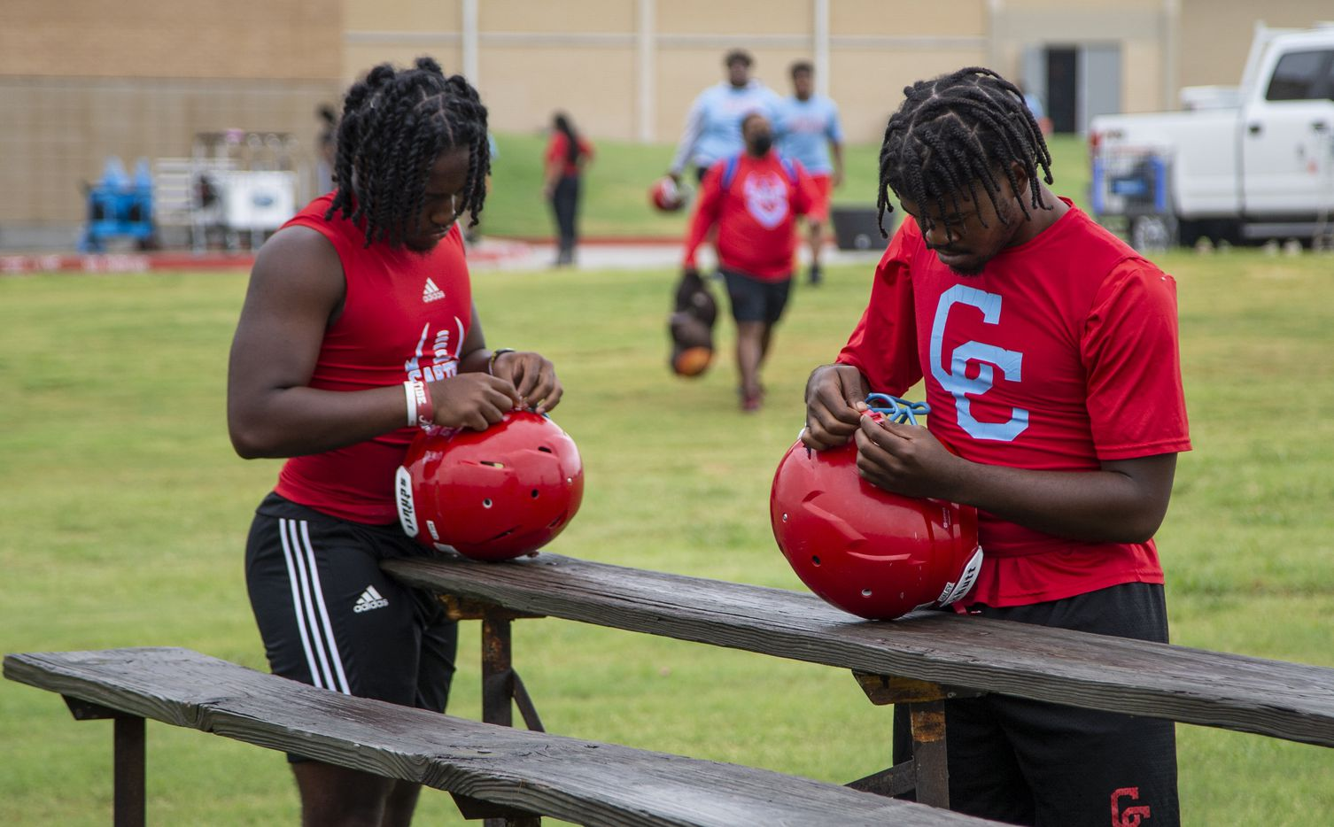 Carter senior receiver Marquis Mills, left, and senior defensive end Solomon Haley adjust their helmets before the start of the first football practice of the season at Carter High School in Dallas, Monday, August 2, 2021. (Brandon Wade/Special Contributor)