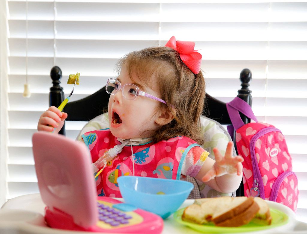 Christina Gregory, who suffers from CCHS (Congenital Central Hypoventilation Syndrome), a genetic disorder that affects her breathing, reacts to her mother as she eats her lunch, Tuesday, January 31, 2017. While she eats, there is a ventilator unit that hooks up to a trachea tube in her neck to assist in breathing when needed.  The Gregory's have two pediatric nurses that keep a watchful eye on Christina at their Southlake,Texas home. The family is affected by Texas' change to their Medicare healthcare coverage, switching to a MCO plan from an HMO plan, limiting their care to within the region -a cumbersome issue for families dealing with 24/7 care. (Tom Fox/The Dallas Morning News)