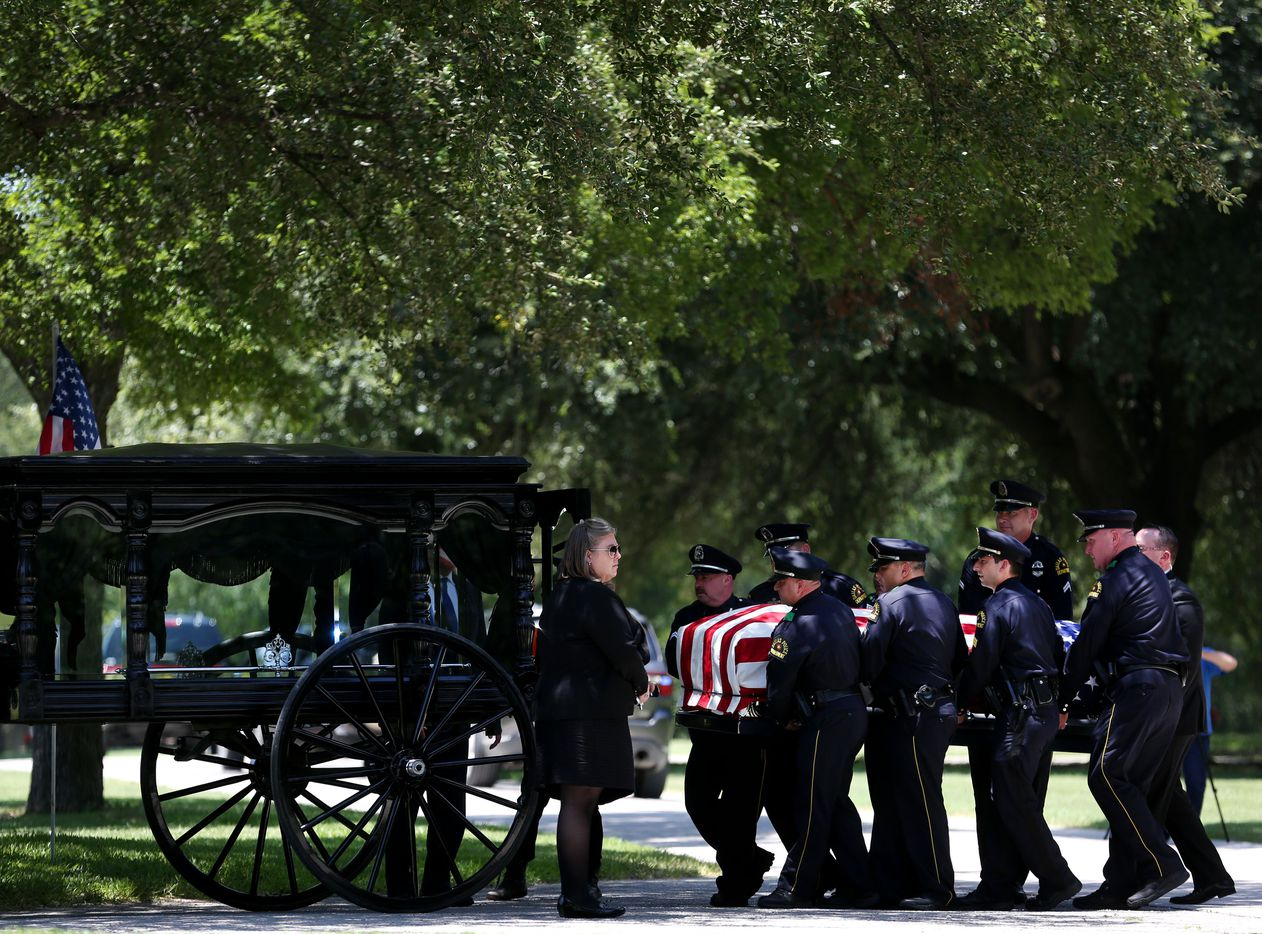 Dallas police officer carry the casket of fallen Dallas police officer Lorne Ahrens into the caisson carriage during his burial at Restland Funeral Home and Cemetery in Dallas on July 13, 2016. Ahrens and four other officers were gunned down during an ambush on police in downtown Dallas.