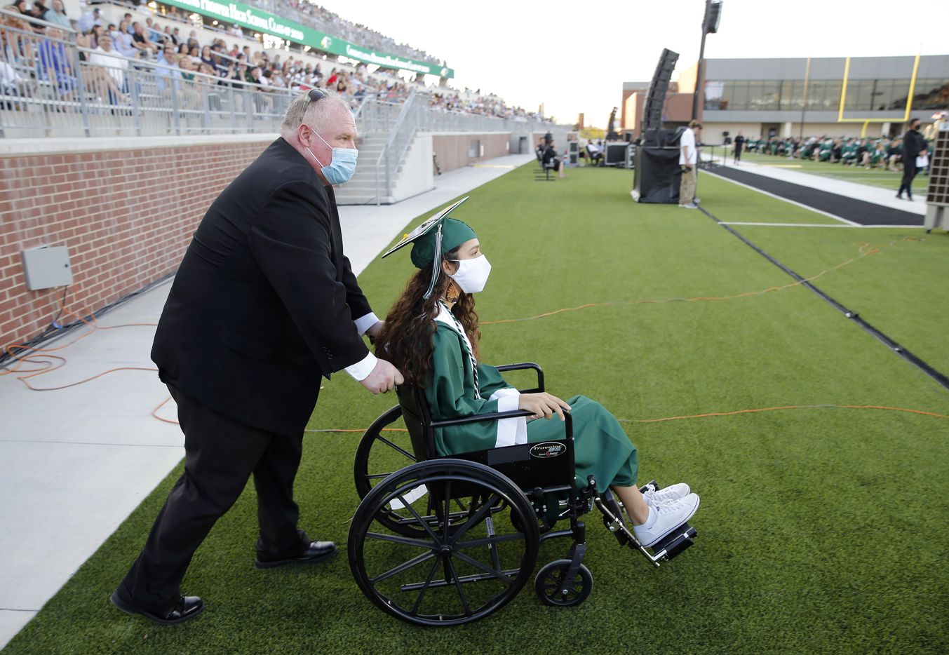 Prosper High School softball player Lexie Bell is pushed towards the stage by Prosper softball coach Todd Rainwater during Prosper High School's graduation ceremony at Children's Health Stadium in Prosper, Texas on Friday, June 5, 2020. Bell signed to play softball at St. Edward's University. But she was recently diagnosed with Ewing Sarcoma, a rare form of cancer.