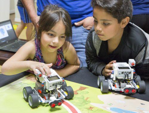 Abigail Vidaña, de 6 años y su hermano Haron, de 8, juegan con autos robóticos durante la presentación del programa Robotix, en el Consulado de México en Dallas. RON HEFLIN/ESPECIAL PARA DMN