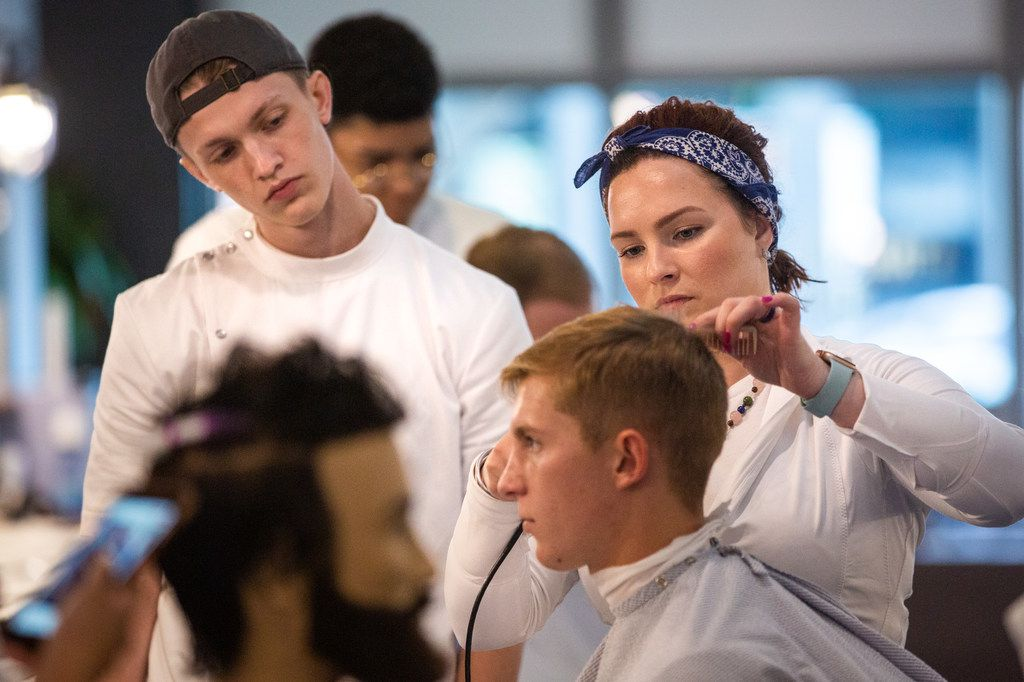Lead educator Nicole McCarter (right) instructs student James Huffman (left) at the Blade Craft Barber Academy.