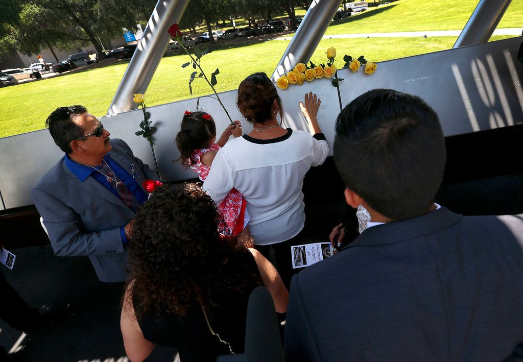 Rogelio Santander (left) and other family members who gathered around the name of his son Wednesday at the Dallas Police Memorial. (Jae S. Lee/Staff Photographer)