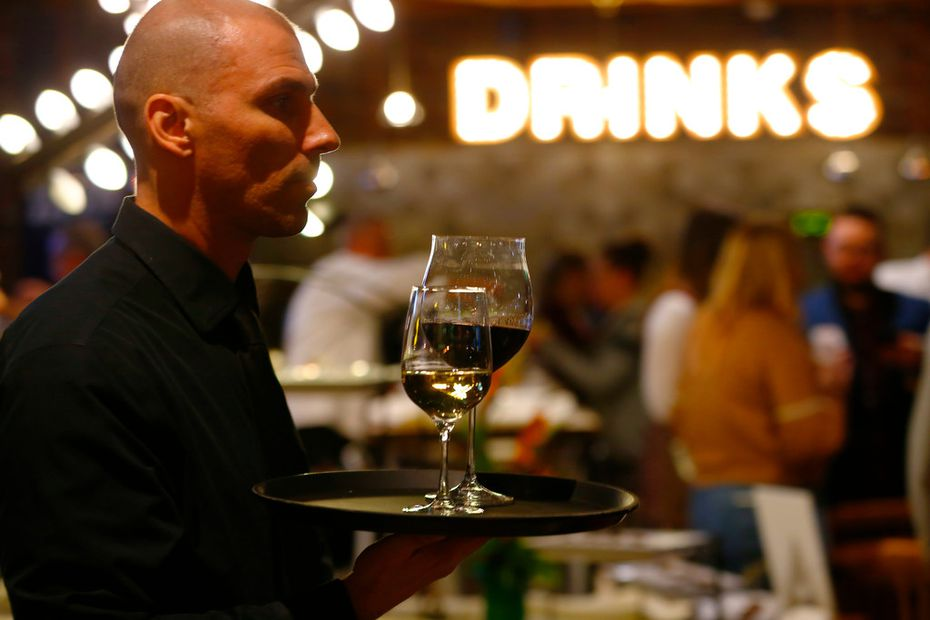 Valerio Dujmovic serves wine at a remodeled and reopened Cafe Express on McKinney Avenue in Uptown Dallas.