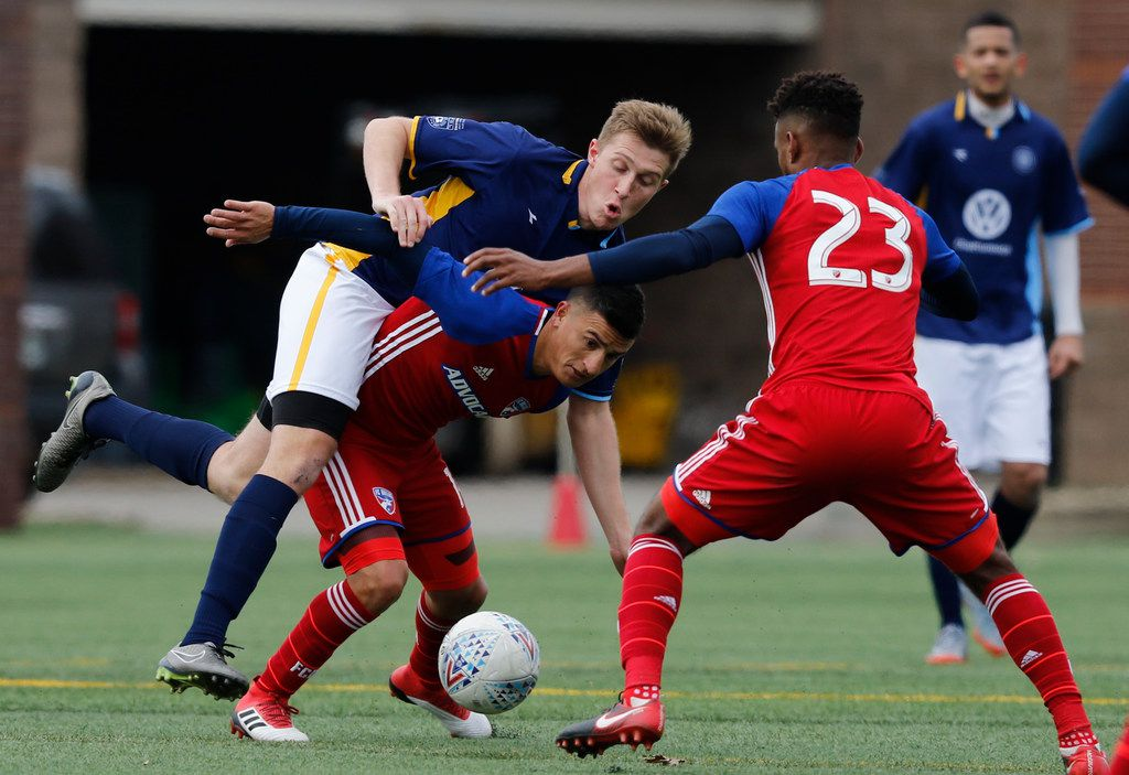 Chattanooga FC's Pierre Bocquet, left, falls over FC Dallas' Mauro Diaz during an exhibition soccer match against at Finley Stadium, Saturday, Feb. 3, 2018, in Chattanooga, Tenn. CFC, a National Premiere Soccer League team of amateur players, held the MLS team FC Dallas to a 1-1 draw. (Doug Strickland/Chattanooga Times Free Press via AP)