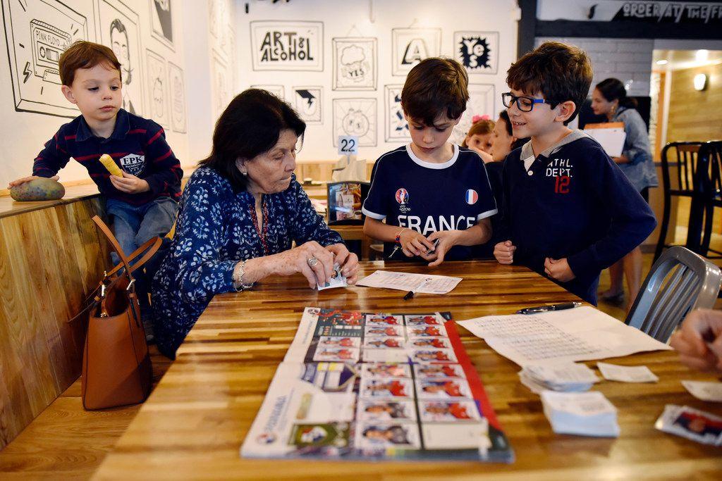 Carmen de Paoli works with a group of kids organizing Panini stickers, including Sebastian del Porto, 4, left, Nicolas del Porto, 8, and Nicolas Lamus, 7, right, at a Panini World Cup sticker album exchange event at Arepa TX in Dalla