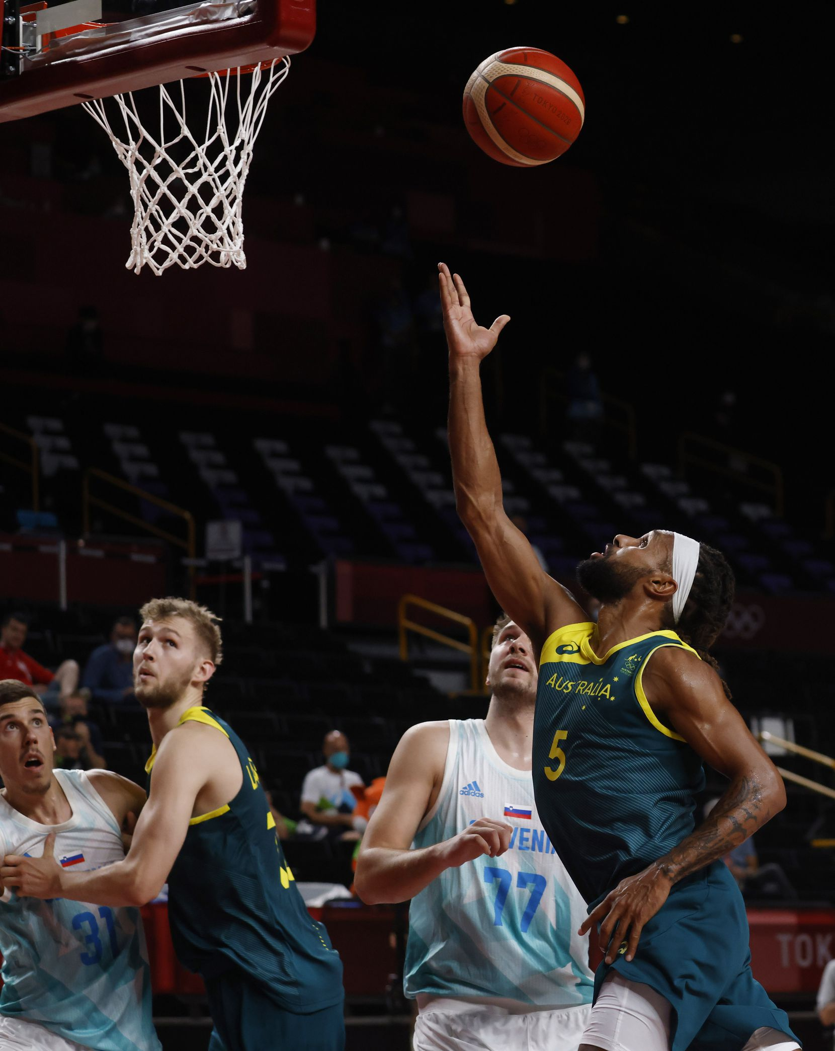 Australia's Patty Mills (5) attempts a layup in front of Slovenia's Luka Doncic (77) during the third quarter of play in the bronze medal basketball game at the postponed 2020 Tokyo Olympics at Saitama Super Arena, on Saturday, August 7, 2021, in Saitama, Japan. (Vernon Bryant/The Dallas Morning News)