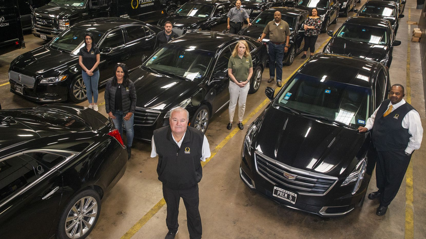 Premier Transportation owner Eric Devlin (center) and his employees pose for a portrait at the company's headquarters in Dallas on Wednesday. Devlin said he's had to lay off 75% of his workforce to keep the company afloat.