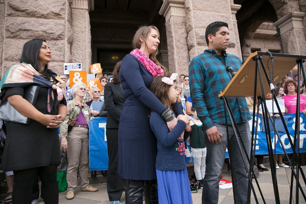 Frank Gonzales, front right, speaks about his daughter, Libby, 6, center, a transgendered child, who stands with her mother, Rachel, during a news conference held by the Transgender Education Network of Texas concerning the 'bathroom bill' at the Capitol in Austin, Texas, Monday, March 6, 2017. (Deborah Cannon/Austin American-Statesman via AP)