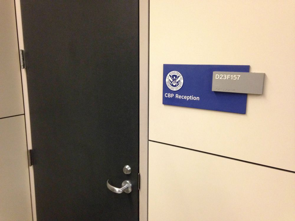 The locked U.S. Customs and Border Protection door at DFW International Airport behind which nine to 11 detainees — most in their 60s and 70s — were being kept from their attorneys Saturday. (Robert Wilonsky/Staff)