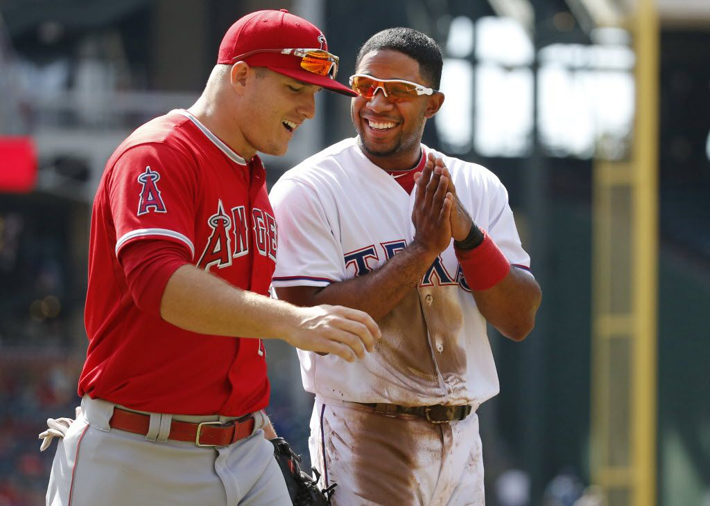 Texas Rangers shortstop Elvis Andrus (1) shares a laugh with Los Angeles Angels center fielder Mike Trout (27) between innings at Globe Life Park in Arlington on Saturday, October 3, 2015.