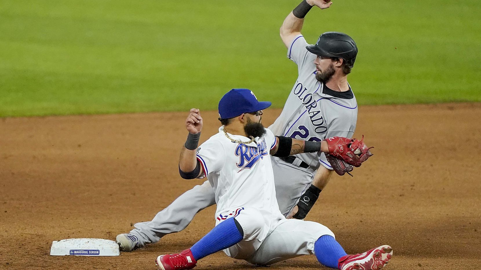 Colorado Rockies center fielder David Dahl slides past the tag from Texas Rangers second baseman Rougned Odor for a stolen base during the ninth inning at Globe Life Field on Saturday, July 25, 2020.