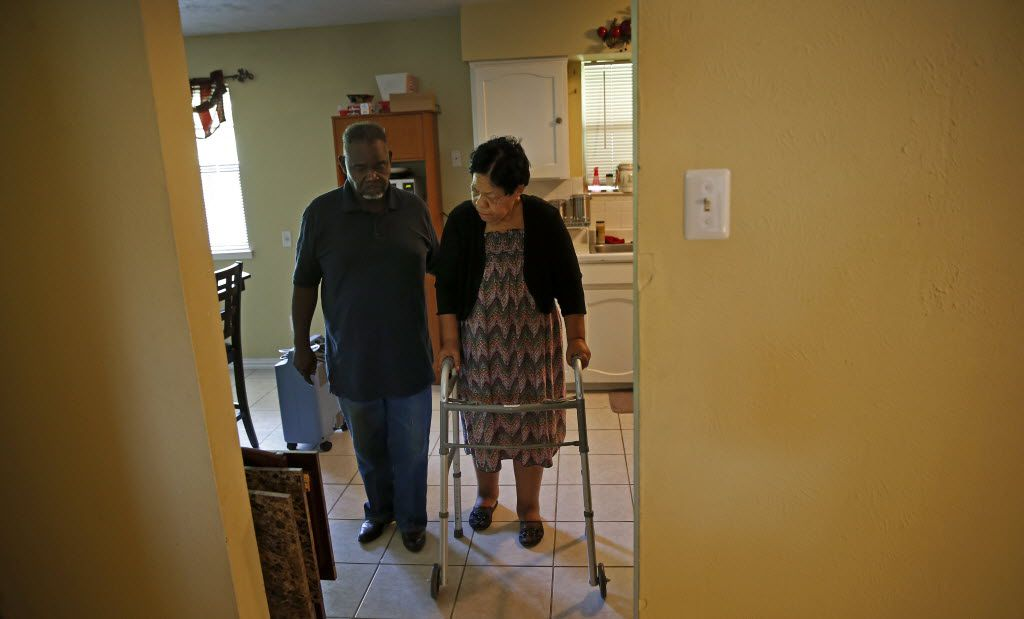 Charlie Wilson helped his wife walk at their home in Duncanville in April. (Jae S. Lee/The Dallas Morning News)