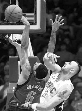 Orlando Magic center Marcin Gortat (right), blocks a shot by Mavericks center Tyson Chandler during the first half of the Magic's 101-76 win on Wednesday. Chandler scored 8 points before leaving with a cut on his hand.