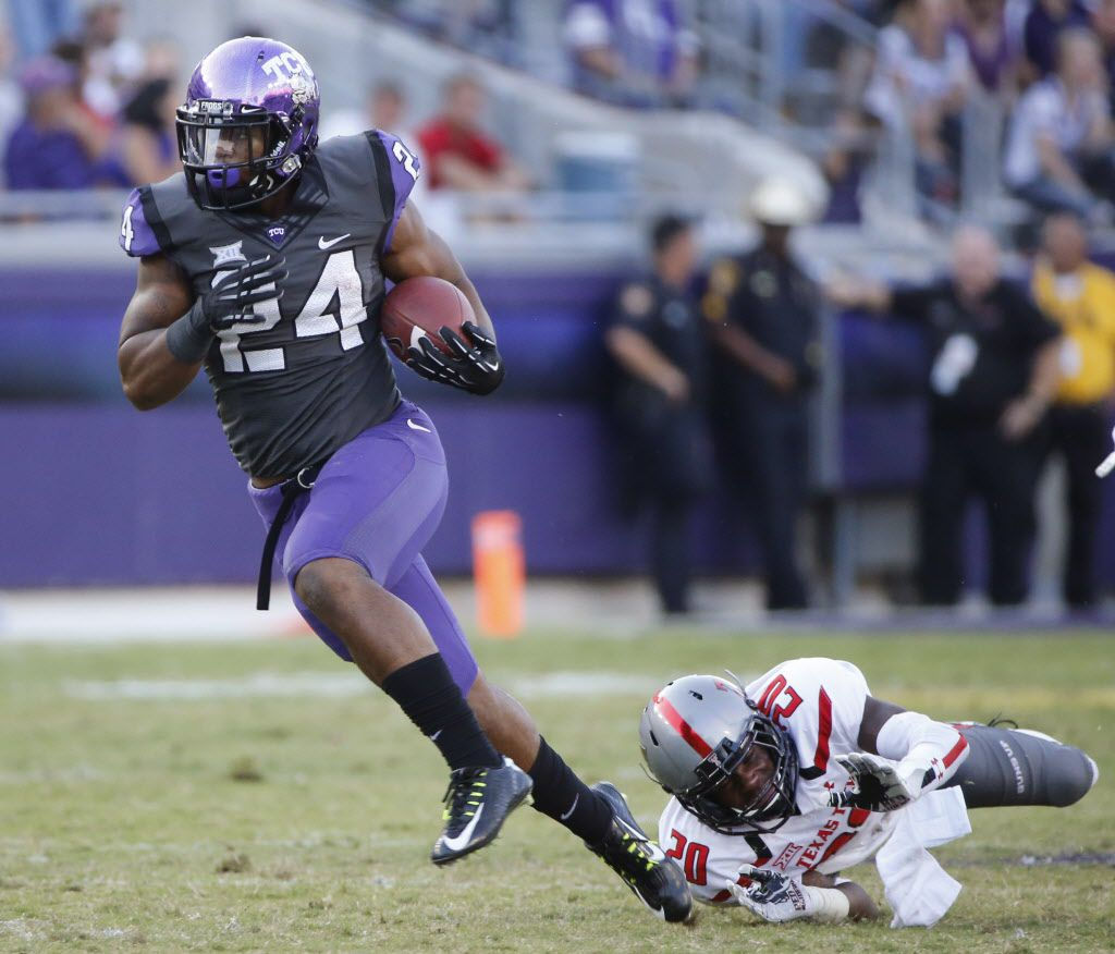TCU running back Trevorris Johnson (24) breaks free from an attempted tackle by Texas Tech defensive back Tevin Madison (20) in the third quarter during the Texas Tech University Red Raiders vs. the TCU Horned Frogs college football game at Amon G. Carter Stadium in Fort Worth on Saturday, October 25, 2014.  (Louis DeLuca/The Dallas Morning News)