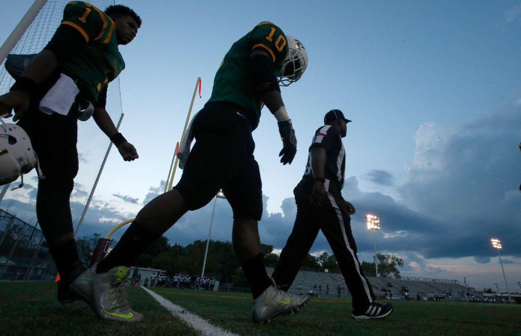 Madison linebacker Kevin Walder (1) and quarterback Travoin Jackson (1) make their way with an official toward midfield for the coin flip against Life Oak Cliff  in the first half of their high school football game at Pleasant Grove Stadium in Dallas, Texas, Friday, September 16, 2016. Mike Stone/Special Contributor