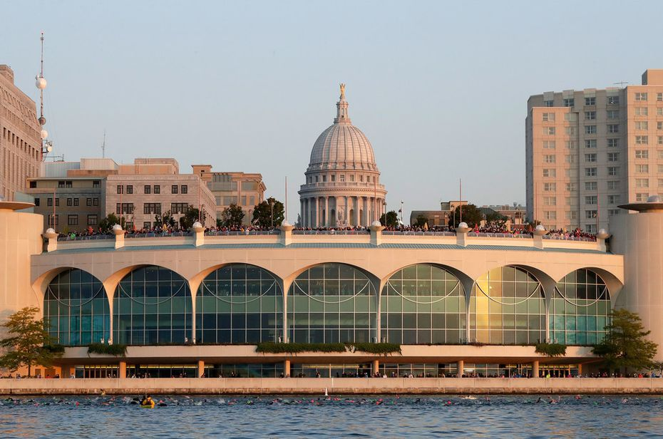 Swimmers pass in front of Monona Terrace in Madison as the Wisconsin state capitol is seen in the background during an Ironman competition in September.