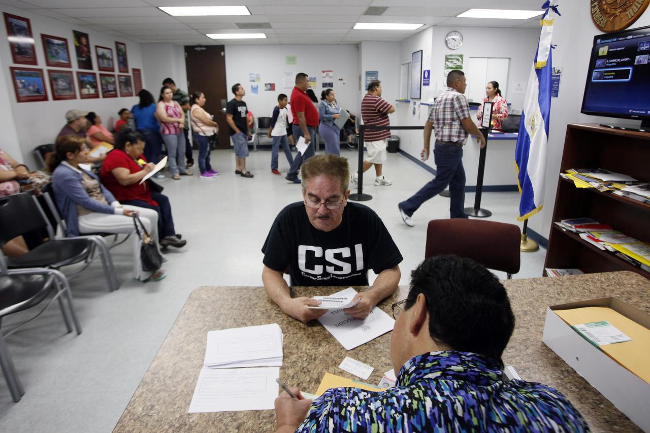 Francisco Álvarez se acerca a platicar con una empleada del consulado salvadoreño en Dallas para recibir ayuda en su reinscripción del TPS. BEN TORRES/AL DÍA