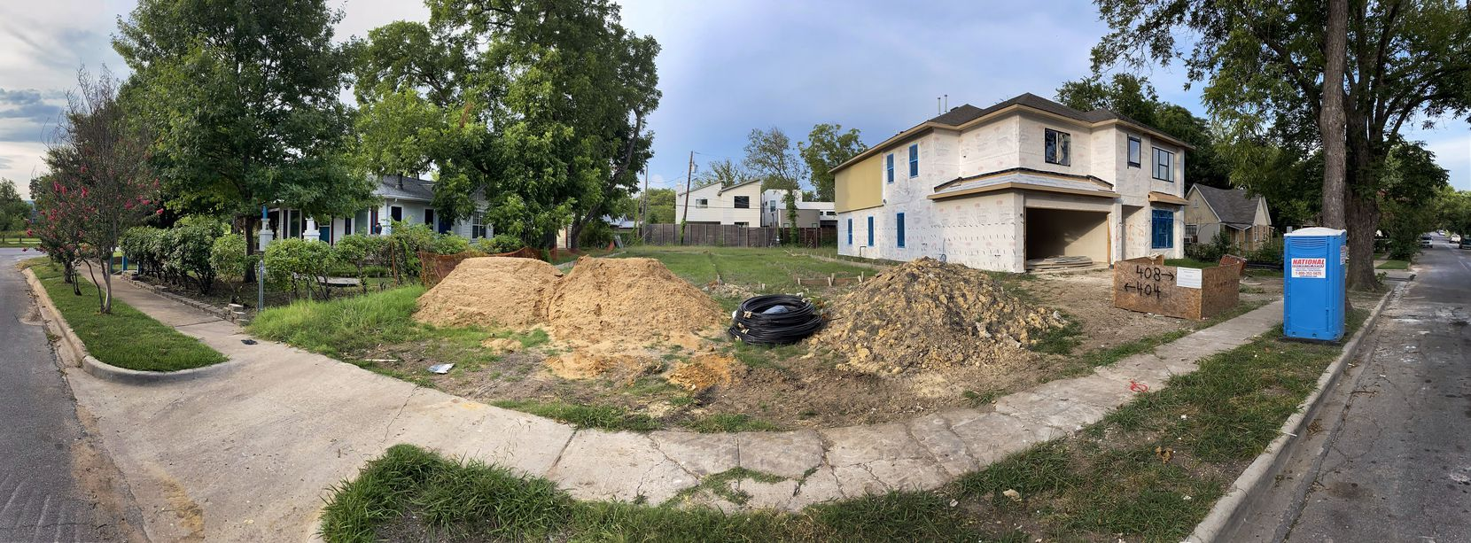 A panoramic view shows a block in which one original-construction house still stands near new construction and a razed lot set to hold another new home.