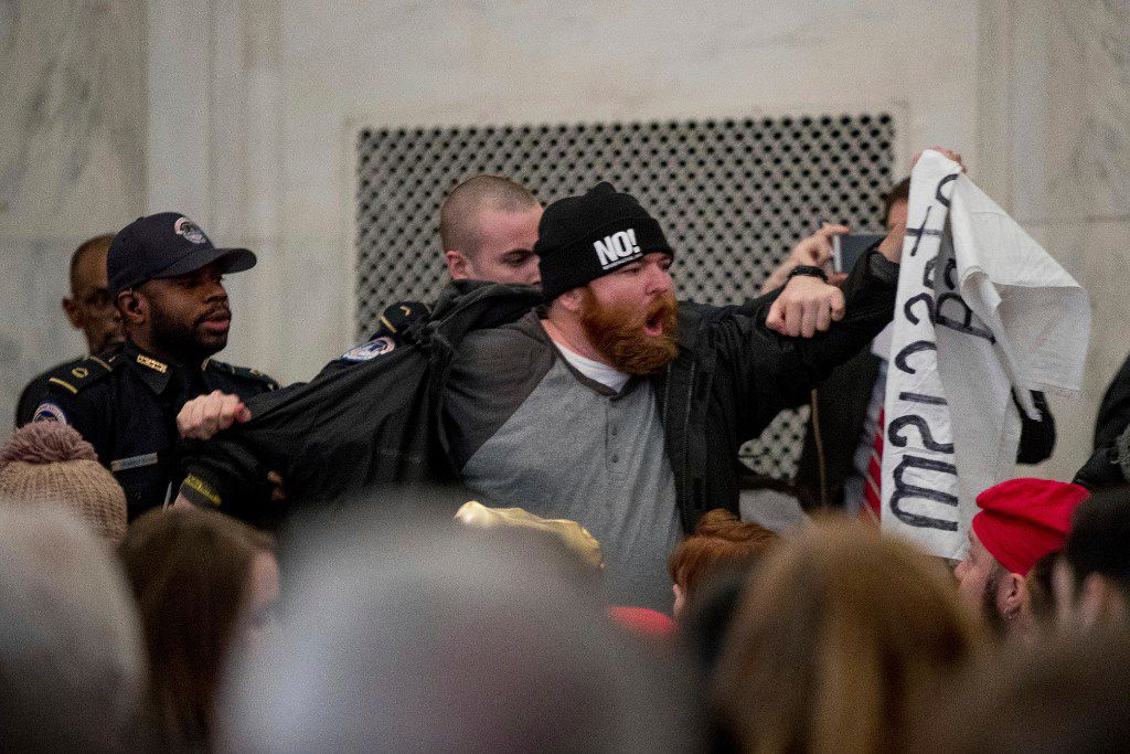 A protester is removed as he disrupts the Senate Judiciary Committee confirmation hearing for Attorney General-designate, Sen. Jeff Sessions, R-Ala.