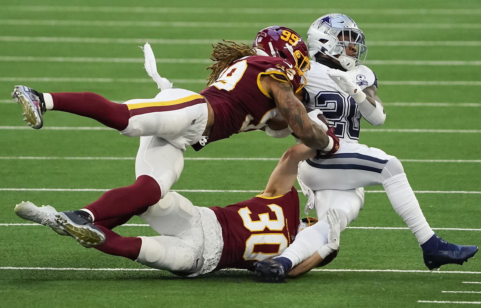 Dallas Cowboys running back Tony Pollard (20) is brought down by Washington Football Team defensive end Chase Young (99) and free safety Troy Apke (30) during the second quarter of an NFL football game at AT&T Stadium on Thursday, Nov. 26, 2020, in Arlington. (Smiley N. Pool/The Dallas Morning News)