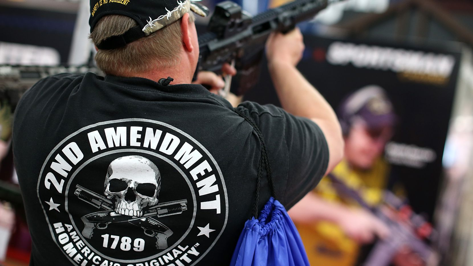 An attendee wears a Second Amendment shirt while inspecting an assault rifle during the 2013 NRA Annual Meeting and Exhibits at the George R. Brown Convention Center in Houston.