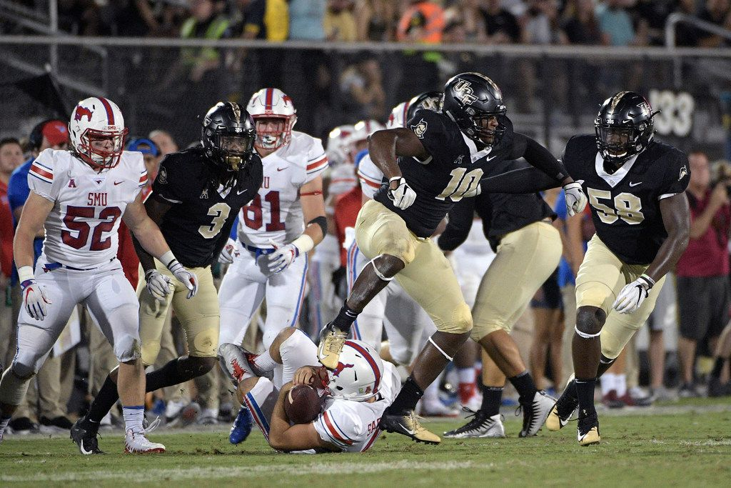 Central Florida defensive lineman Titus Davis (10) celebrates after stopping SMU punter Jamie Sackville, below, short of a first down on a fake punt play during the second half of an NCAA college football game Saturday, Oct. 6, 2018, in Orlando, Fla. UCF won 48-20. (AP Photo/Phelan M. Ebenhack)