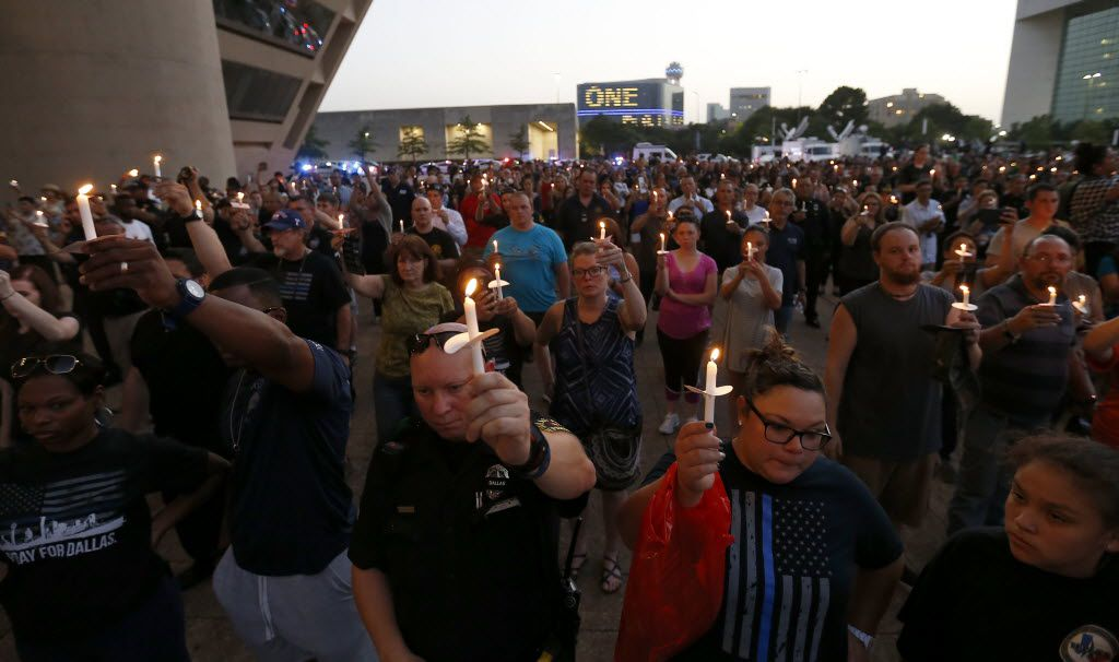 Dallas police officers and other people hold candles during a candlelight vigil hosted by the Dallas Police Association in honor of the five police officers killed by the ambush attack in the line of duty at Dallas City Hall in downtown Dallas, Monday, July 11, 2016. (Jae S. Lee/The Dallas Morning News)