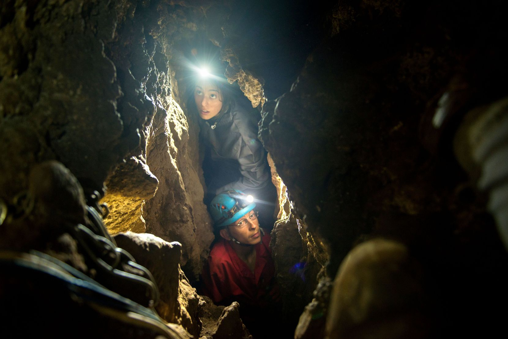 Megan Berger (top, who is Lee Berger's daughter) and Rick Hunter squeeze through an opening as the scientific team ventures deep into the chambers of the Rising Star cave system.