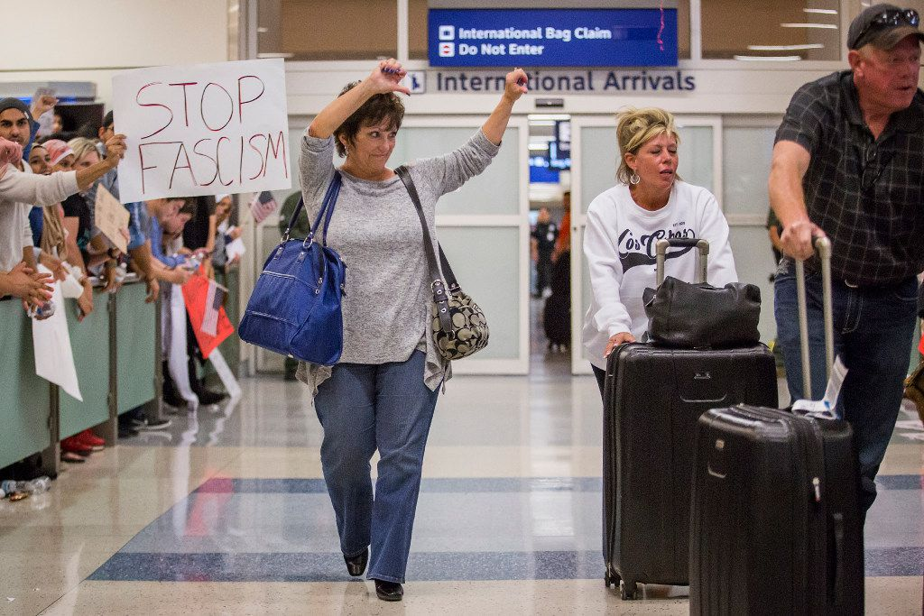 A woman exiting the arrivals hall gives a thumbs down to protestors at DFW International Airport in opposition to President Donald Trump's executive order on Sunday, Jan. 29, 2017.