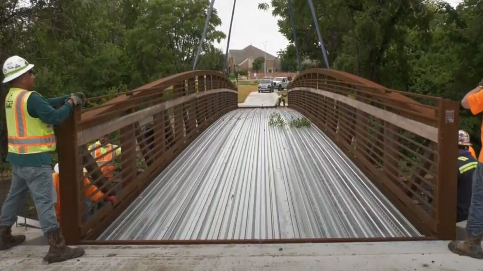 Workers admire one of three new pedestrian bridges that were installed along Legacy Trail in Plano.