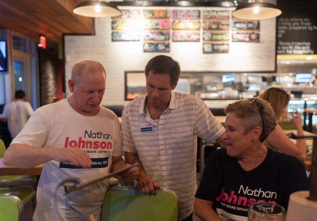 Nathan Johnson, center, talks with Brad Carafiol, left, at Hopdoddy Burger Bar after he and other volunteers  canvassed a neighborhood on Monday, Sept. 3, 2018.  He is running against Don Huffines for the Texas Senate in district 16. (Rex C Curry/Special Contributor)