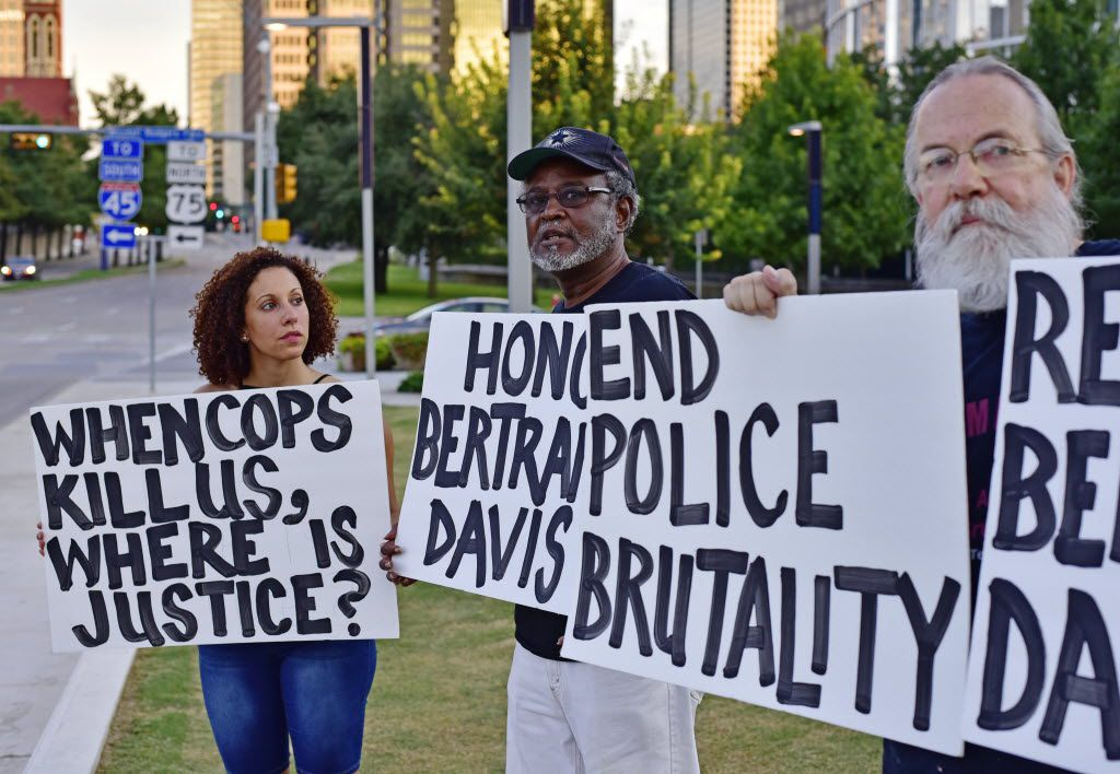 Sara Mokuria, co-founder of Mothers Against Police Brutality, holds a sign during an August memorial service for Bertrand S. Davis. His father, Otis Davis, stands in the middle with John Fullinwider, another co-founder of the anti-brutality group.