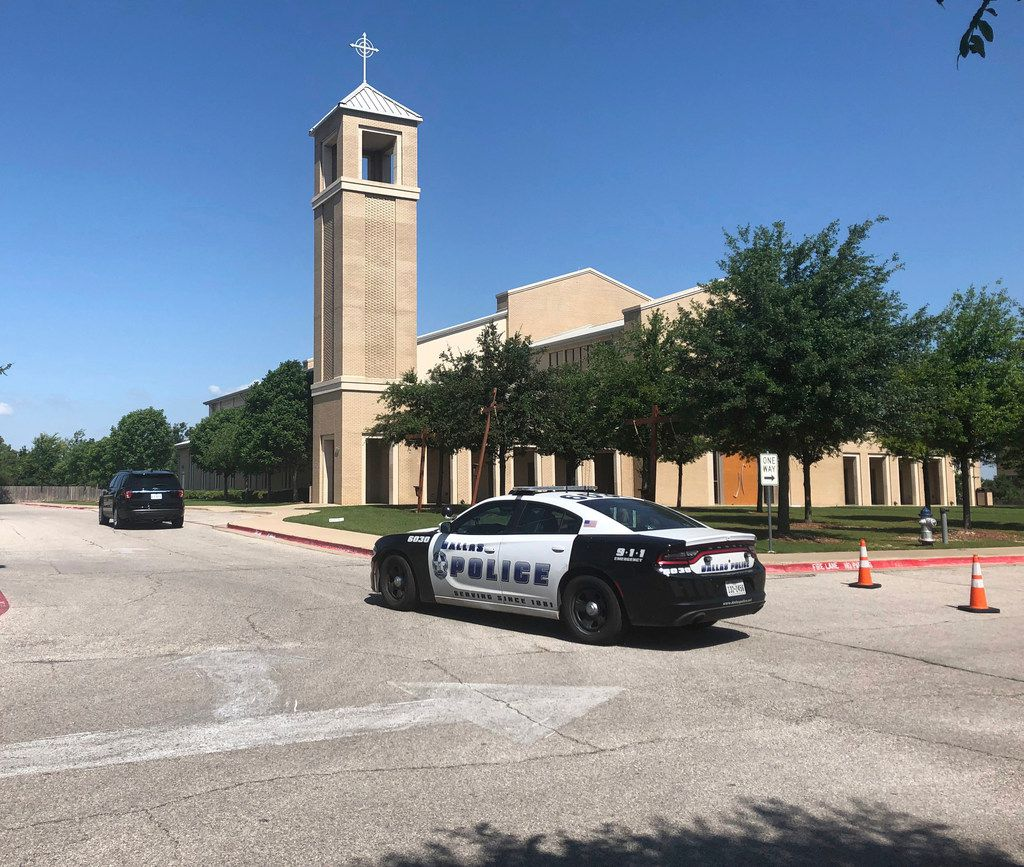 A Dallas police vehicle was parked outside St. Cecilia Catholic Church on May 15, the day officers raided several diocese offices.