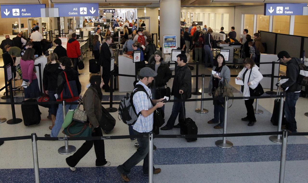 Travelers wait in line to go through security at Terminal D at DFW International Airport.