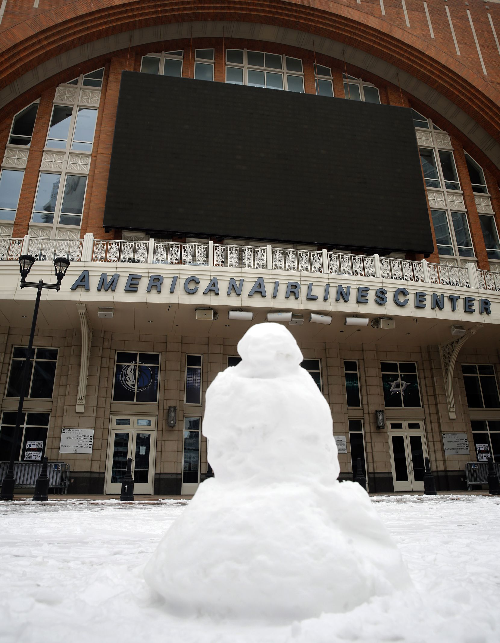 Someone built a snowman on Victory Plaza outside the American Airlines Center in Dallas,  Tuesday, February 16, 2021. Because of the widespread loss of electricity from the snow storm, the Dallas Stars and Dallas Mavericks have canceled games at the darkened arena. (Tom Fox/The Dallas Morning News)