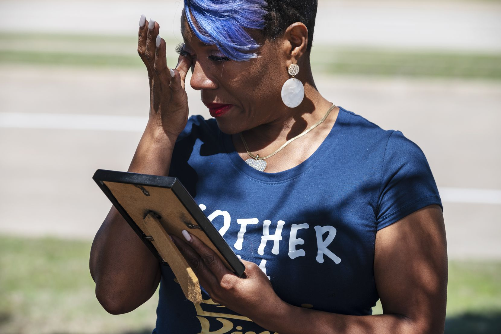 Donna Fields, 47, wipes away tears while looking at a photo of her son Marcus Bell Jr., when he was 12 years old. Bell says he was raped by Pastor Rickie Rush when he was 13. Fields and her sister also say Rush sexually assaulted them.