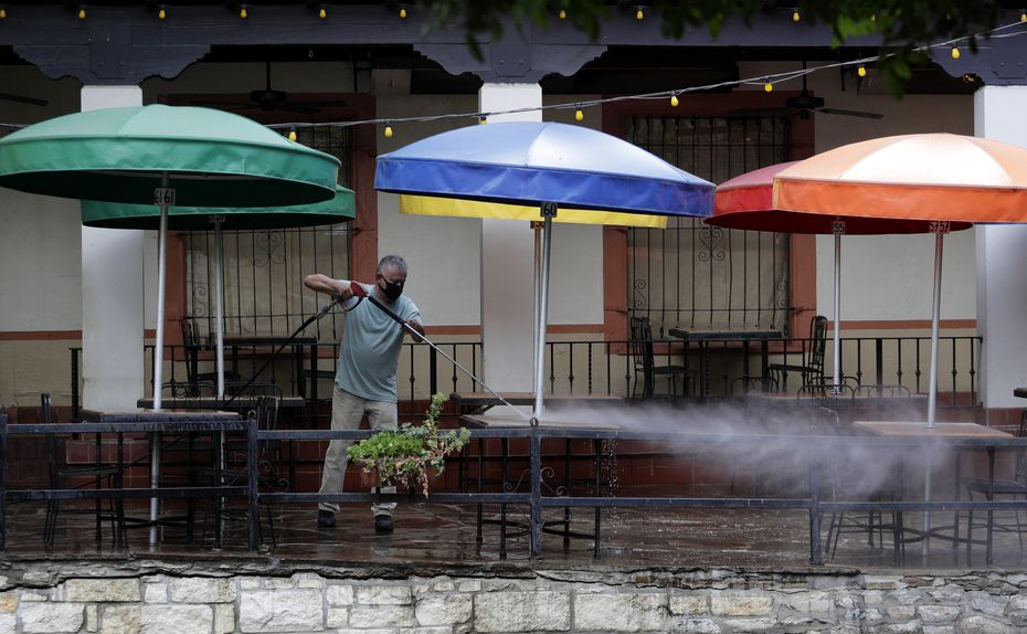 Workers clean the patio seating area of a restaurant on the River Walk that is preparing to open soon, Tuesday, May 12, 2020, in San Antonio. The restaurant has been closed due to the COVID-19 pandemic and will open with limited seating and make use of social distancing practices.