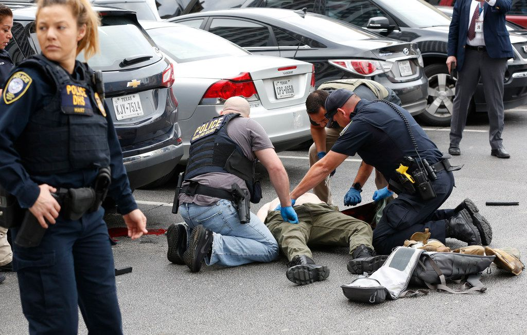 Law enforcement hovers over the shooter in a parking lot after he fired shots Monday morning, June 17, 2019 at the Earle Cabell federal courthouse in downtown Dallas. Law enforcement returned fire and the shooter was hit by gunfire. No officers or citizens were injured. (Tom Fox/The Dallas Morning News)  - MANDATORY CREDIT; NO SALES; MAGS OUT; TV OUT; INTERNET USE BY AP MEMBERS ONLY